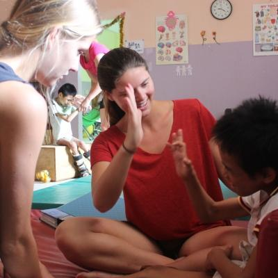 Australian intern with Projects Abroad talking to a young local boy whilst on her occupational therapy work experience in Cambodia.